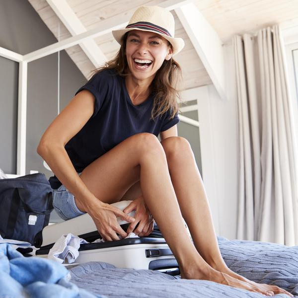 Portrait Of Woman Trying To Close Full Holiday Suitcase