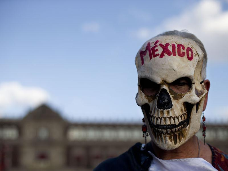 A woman wears a skull mask as she stands in front of the National Palace during a rally by relatives and supporters of 43 missing teacher's college students in the Zocalo, Mexico City's main square, in 2015.