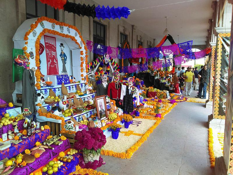 Day of the Dead in Mexico is a time to visit cemeteries, light candles, and bake food for the dead.